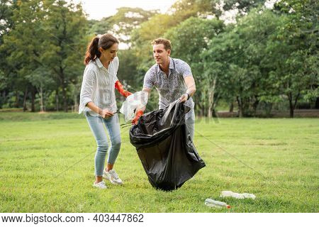 Volunteer Lovers Couple Wearing Gloves Walking To To Pick Up Garbage In The Park To Keep The Environ