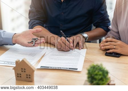 Young Asian Man Signing A Contract For Buying House In Office Of Estate Agent And Real Estate Agent