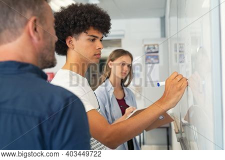 Young african man solving mathematics problem. College student solving algebra equation on white board in classroom. High school black guy trying to understand mathematics problem during lesson.