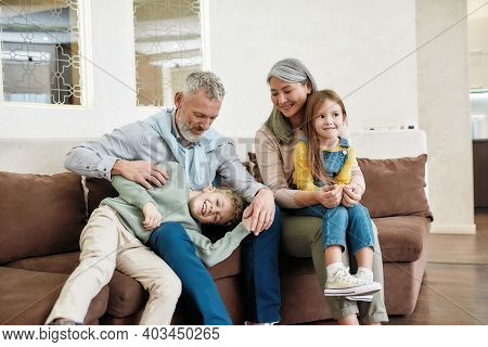 Portrait Of Lovely Happy Family, Grandparents And Grandchildren Having Fun And Relaxing While Sittin