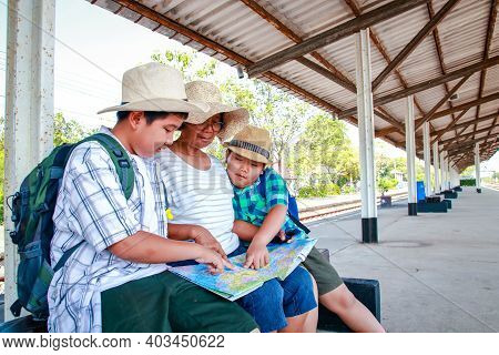 Grandma And Nephew Sitting To Wait For The Train At The Station. In Order To Travel