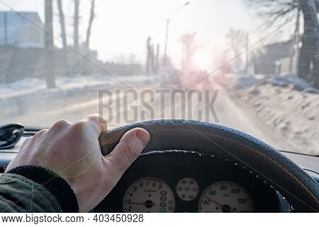 A Dangerous Road, A Man Hand On The Steering Wheel Of A Car That Is Driving On A Snow Covered Slippe