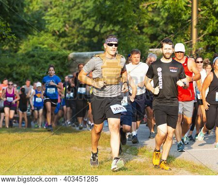 North Babylon, New York, Usa - 8 July 2019: A Runner Racing A 5k In A Weight Vest Running On The Gra