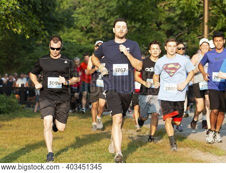 North Babylon, New York, Usa - 8 July 2019: Front View Of Runners Racing In A Crowded 5k Race Steppi