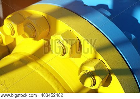 Two Blue And Yellow Gas Pipes Are Connected By Large Bolts And Nuts. Background For Suppliers Of Gas