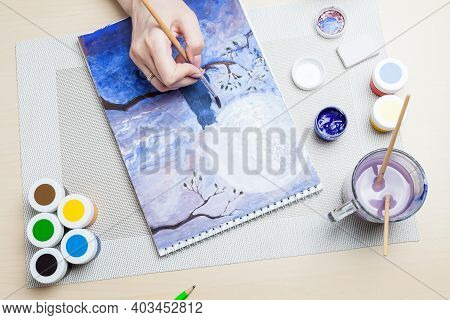 A Close-up Of Female Hands Over A Painted Picture Holding A Brush And A Cover For Watercolors On Whi