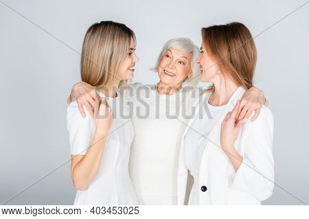 Three Generation Of Cheerful Women Smiling While Hugging Isolated On Grey