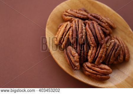 Pecan Nut Close-up In Spoon On Brown Background.healthy Fats.heap Shelled Pecans Nut . Ingredient Of