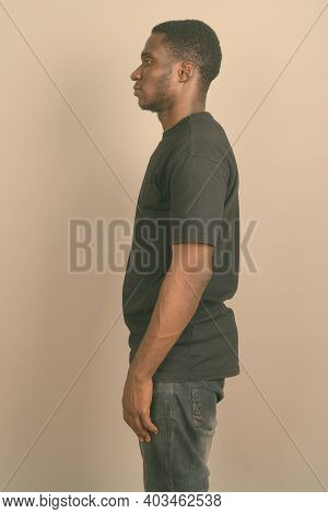 Young African Man Wearing Black Shirt Against Gray Background