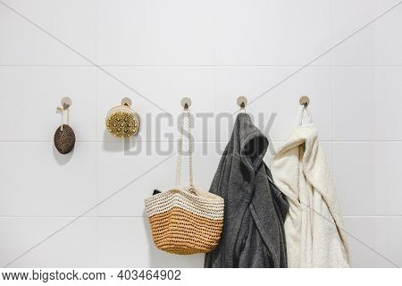 Two Bathrobes, A Basket And Sustainable Zero Waste Bathroom Accessories On A White Wall. Sustainable