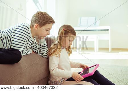 Happy Siblings Children Playing With Tablet On Floor At Home