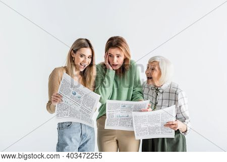 Three Generation Of Astonished Women Reading Newspapers Isolated On White