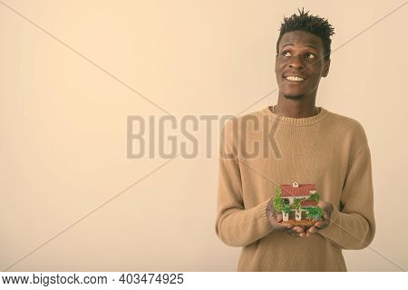 Studio Shot Of Young Happy Black African Man Smiling And Thinking While Holding House Figurine Again