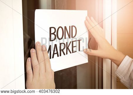 Closeup Of Owner Holding Text Bond Market In Store