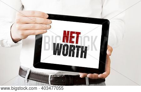 Text Net Worth On Tablet Display In Businessman Hands On The White Bakcground. Business Concept
