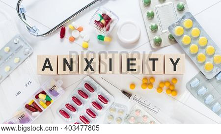 Anxiety Word On Wooden Blocks On The Table. Medical Concept With Pills, Vitamins, Stethoscope And Sy