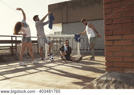 Group Of Young Friends Stretching Out And Warming Up Before Playing Football On Building Rooftop Ter