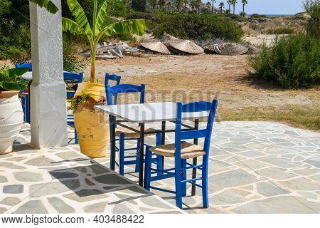 Ios, Greece - September 21, 2020: Table And Chairs In Greek Restaurant At Manganari Beach On Ios Isl