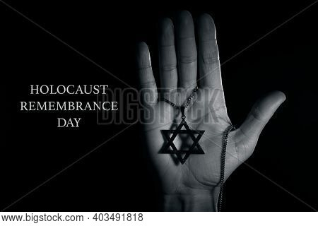 closeup of an old and rusty pendant in the shape of the star of david on the hand of a man and the text holocaust remembrance day on a black background