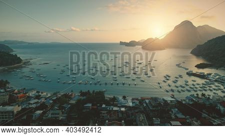Ocean bay aerial view of sunset at port with water transport at tropical cityscape. Paradise city of Philippines islands. Greenery mount with forest trees at summer sunny day. Cinematic drone shot