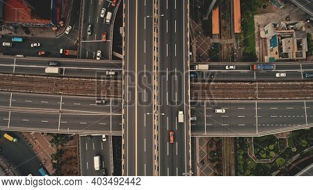 Top down cross traffic highway with cars, trucks aerial. Urban transportation at bridge road at metropolis city of Manila, Philippines, Asia. Cinematic cityscape of downtown freeway drone shot