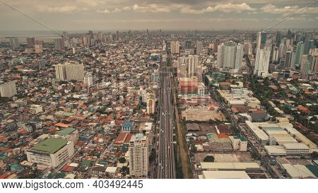 Top down car park at high buildings, freeway with cars and trucks. Downtown traffic road at cityscape urban scenery in aerial view. Local transportation of Philippine capital Manila town drone shot
