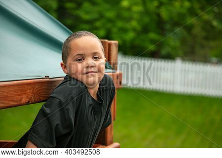 Handsome Hispanic African American boy in a play fort