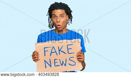 Young african american man holding fake news banner scared and amazed with open mouth for surprise, disbelief face