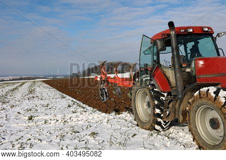 Tractor At Work Plowing A Field In Winter.