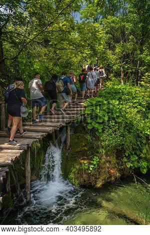 Plitvicka Jezera, Croatia, July 2019 Crowd Of Tourists Walking On Boardwalk In Stunning Plitvice Lak