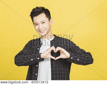Happy Young Man Showing Heart And Love Shape Gesture