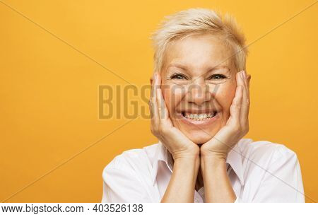 Life only starts when get older. Portrait of happy and charming european senior woman with blond short hair laughing and amusement holding palms on cheeks over yellow background