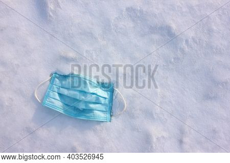 Used Pandemic Face Mask Discarded On The Ground Covered With Snow. Protective Mask On White Backgrou