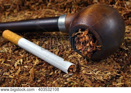 Smoking Pipe And Cigarette. Cigarette And Smoking Pipe On Tobacco Leaves Close-up. Bad Habits
