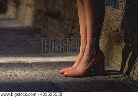 Young Lady In Beige Leather Heels Standing On The Pavement On The City Street. Casual Street Fashion