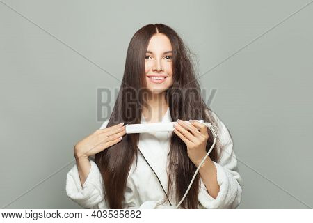 Healthy Brunette Woman Straighten Her Hair With Straightener On White Background. Haircare Concept