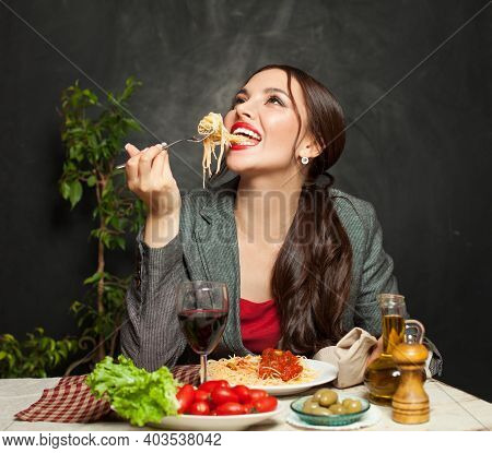 Happy Young Woman Eating Pasta In Restaurant
