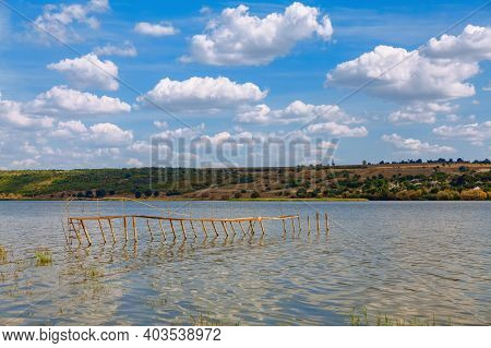 Wooden Pillars Of Old Pier . Rustic Riverside Scenery