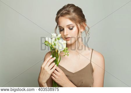 Healthy Young Woman Holding White Flowers On White Background