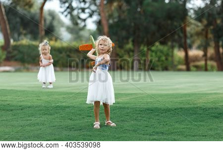 Little Girl In Dress Launches A Toy Plane Into The Air In The Park Outdoor,on Background Blurred You