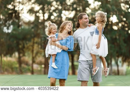 Parents Hold Daughters In Their Arms In Countryside, Enjoing Time Together. Happy Family Concept. Bl