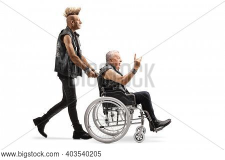 Man in leather clothes with a mohawk pushing a mature punk in a wheelchair isolated on white background