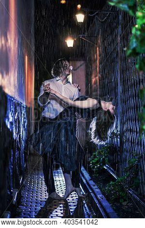 Young Pair Dancing Under The Night Rain. Lantern Lights, Wet Clothes And Surfaces, Male And Female W