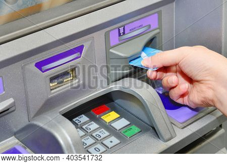 Hand Of A Woman With A Credit Card, Using An Atm. Woman Using An Atm Machine With His Credit Card