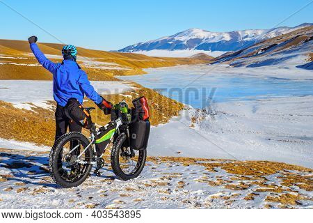 Male Traveler On A Bicycle In Winter In The Mountains. Winter Travel. High-mountain Plateau Turgen-a