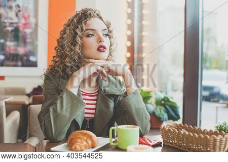 Romantic Woman Drinking Coffee And Looking Out The Window In Cafe