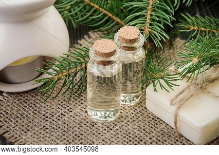 Spruce Essential Oil In Two Bottles On Linen Napkin, Natural Soap, Aroma Lamp And Fir Branches Aroun