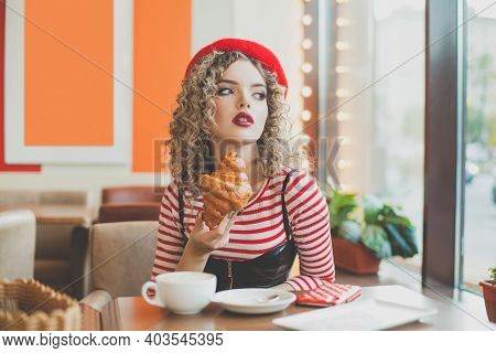 Cheerful Woman Drinking Coffee And Looking Out The Window In Cafe