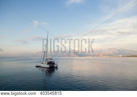 Catamaran Yacht In The Tropical Sea At Sunset Panorama. Yachting, A Luxury Sailing Theme In Turkey.