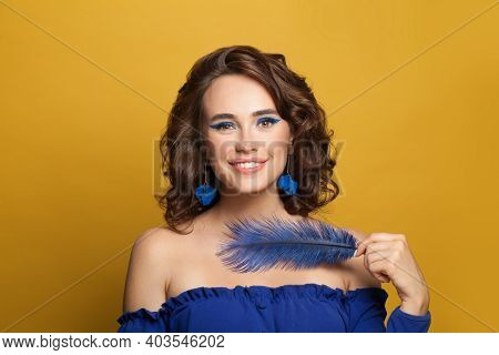 Brunette Model Woman Holding Blue Feather On Yellow Background